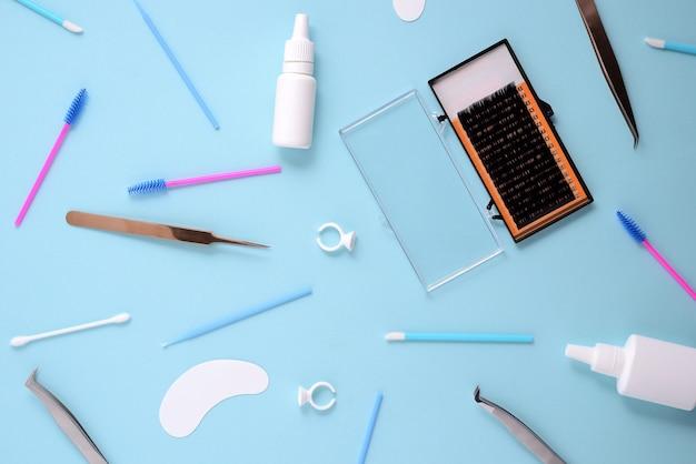 Pennelli trucco e cosmetici su sfondo blu. vista dall'alto, piatta distesa