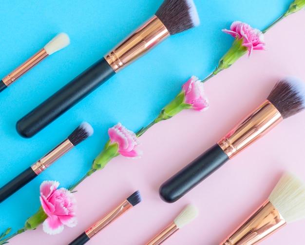 Pennelli trucco premium, palette di ombretti e fiori su uno sfondo colorato di blu e rosa, cosmetici creativi piatti distesi con composizione diagonale