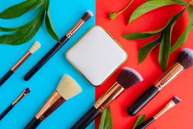 Pennelli trucco premium, tavolozza ombretti e foglie su uno sfondo colorato di blu e rosso, cosmetici creativi piatti distesi con composizione diagonale