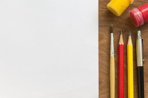 Pennello, acquerello, matita, penna con carta bianca sul tavolo in legno, concept creativo.