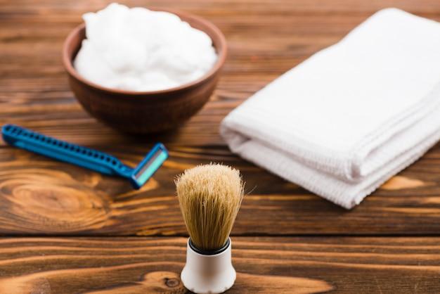 Pennello da barba classico davanti alla ciotola di schiuma; tovagliolo bianco piegato e rasoio sulla scrivania in legno