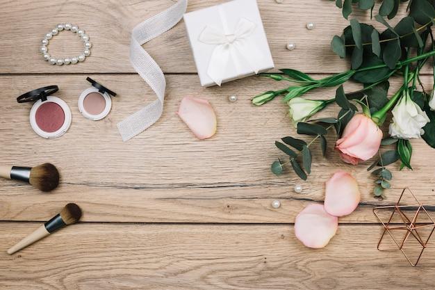 Pennello da trucco; cipria compatta; perle; pacco regalo; rosa e fiori eustoma sulla scrivania in legno