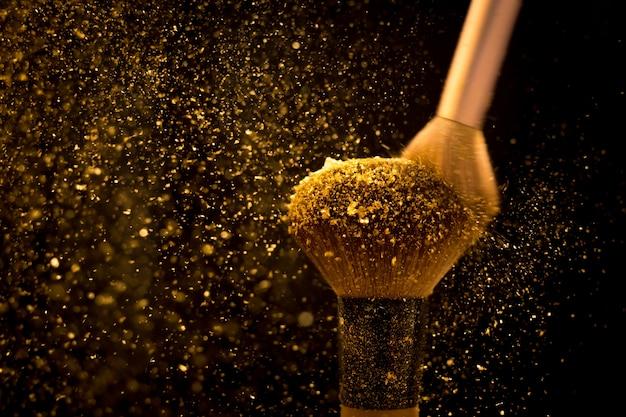 Pennello da trucco con polvere cosmetica dorata