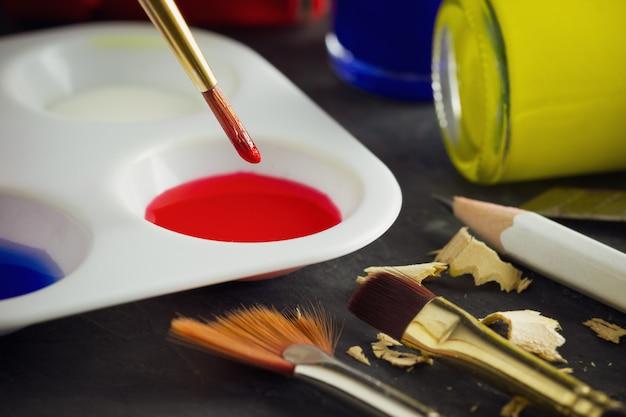 Pennello dell'artista del primo piano sopra la bottiglia di colore del piatto e del manifesto di colore sulla tavola