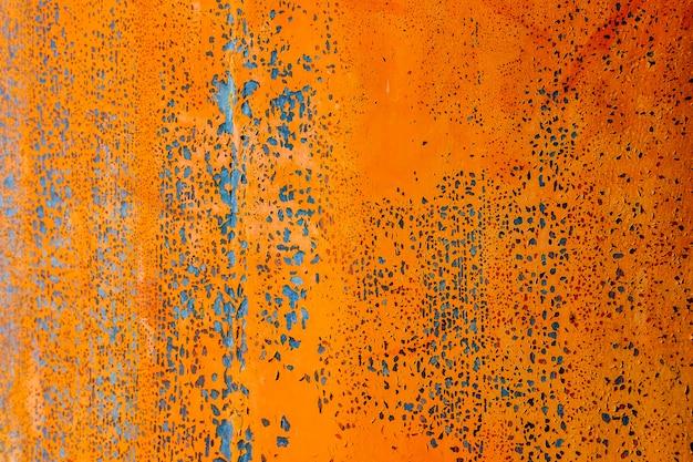 Pennello di colore arancione sulla piastra in acciaio arrugginito e ruvido per lo sfondo