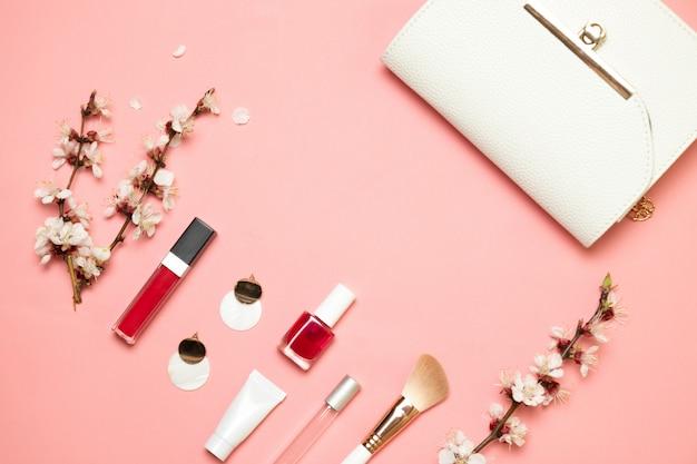 Pennello e cosmetica e bianca piccola borsa alla moda su sfondo chiaro corallo vivente