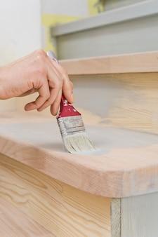 Pennello in mano, applicare la vernice su una superficie di legno durante la riparazione
