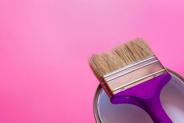 Pennello viola con scatola aperta di vernice bianca,