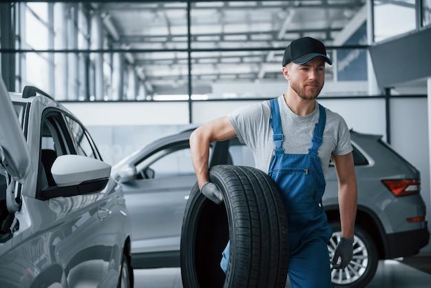Pensando a cosa fare dopo. meccanico in possesso di un pneumatico presso il garage di riparazione. sostituzione di pneumatici invernali ed estivi