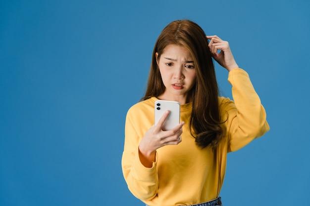 Pensando che sogna la giovane signora dell'asia che utilizza il telefono con l'espressione positiva, vestita in felicità di sensazione dell'abbigliamento casual e sta isolata su fondo blu. la donna felice adorabile felice si rallegra del successo.