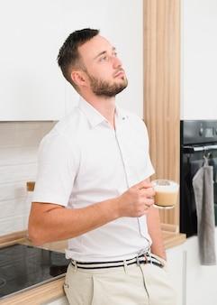 Pensatore uomo in cucina con un cappuccino