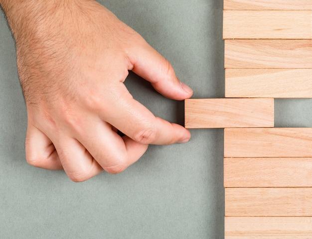 Pensiero differente e concetto differente di idea con i blocchi di legno sulla vista superiore del fondo di verde navy. uomo che fa scorrere l'elemento. immagine orizzontale