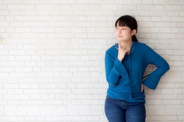 Pensiero sicuro della giovane donna asiatica del bello ritratto con il fondo del calcestruzzo e del cemento