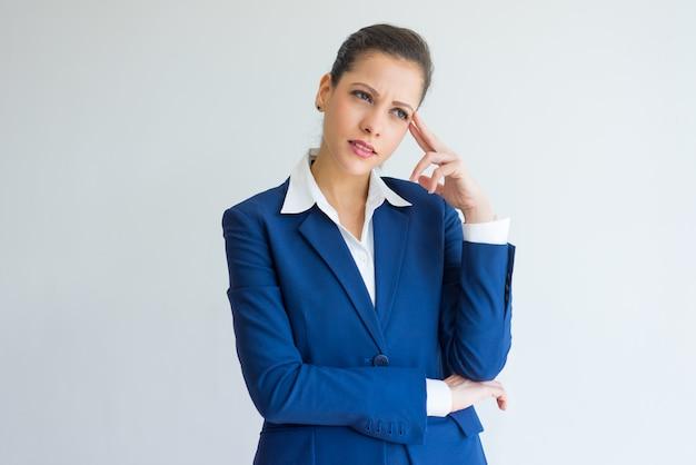 Pensieroso giovane donna d'affari pensando intensamente.