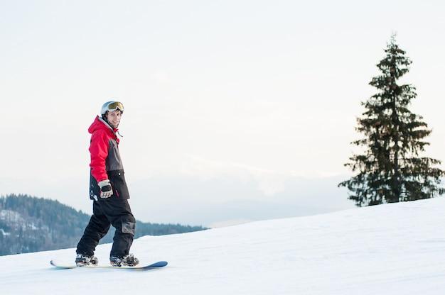 Pensionante maschio sul suo snowboard al resort winer