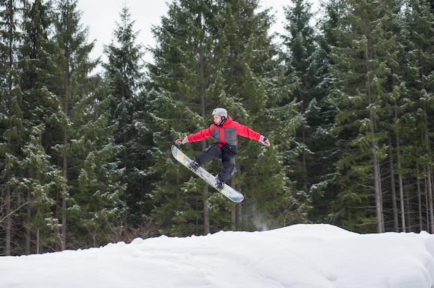 Pensionante maschio sullo snowboard che salta il pendio in inverno