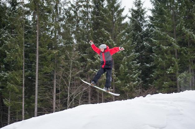 Pensionante maschio sullo snowboard che salta sopra il pendio