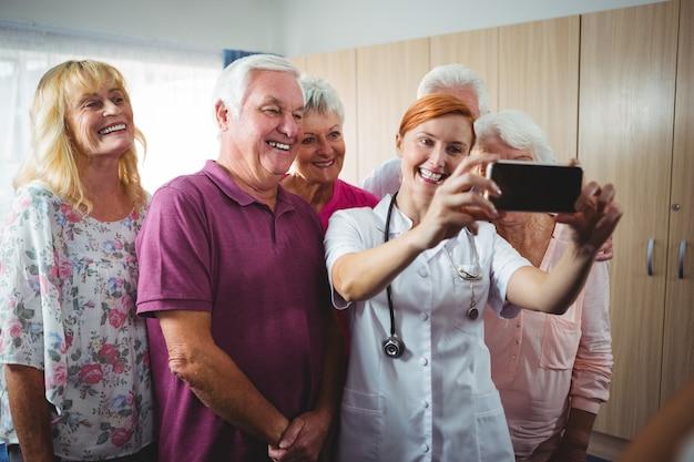 Pensionati che prendono un selfie con un'infermiera