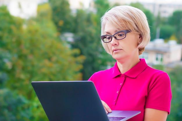 Pensionato senior maturo colpito sorpreso della donna con i vetri che lavora al computer portatile con lo sguardo sorpreso di meraviglia. free lance pensionate anziane che per mezzo del computer del pc, digitando all'aperto. vecchia generazione, tecnologie.