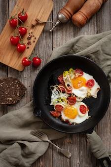 Pentola con uova fritte e pomodorini su fondo rustico.