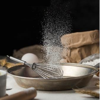 Pentola di cottura del primo piano con la frusta e lo zucchero