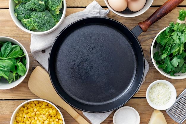 Pentola di cottura vuota con gli ingredienti per la cottura delle uova sane della prima colazione con i broccoli, gli spinaci ed il formaggio sulla vista di legno del piano d'appoggio