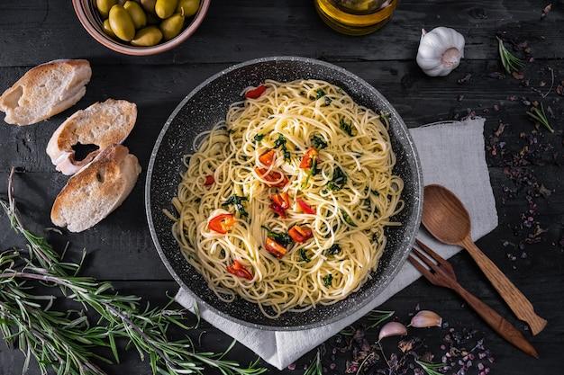 Pentola di pasta italiana cotta, vista dall'alto. disposizione piana del pasto tradizionale degli spaghetti con le verdure, l'aglio e le olive su superficie rustica nera