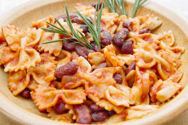 Pentola di terracotta con pasta italiana con fagioli rossi