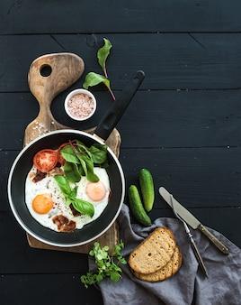 Pentola di uova fritte, pancetta, pomodori con pane, barbabietola e cetrioli su tavola di servizio in legno rustico sulla superficie del tavolo scuro