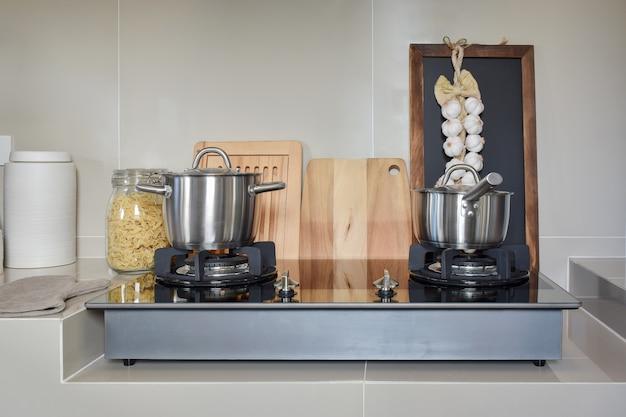 Pentola in acciaio inox sul fornello a gas con utensili in cucina moderna