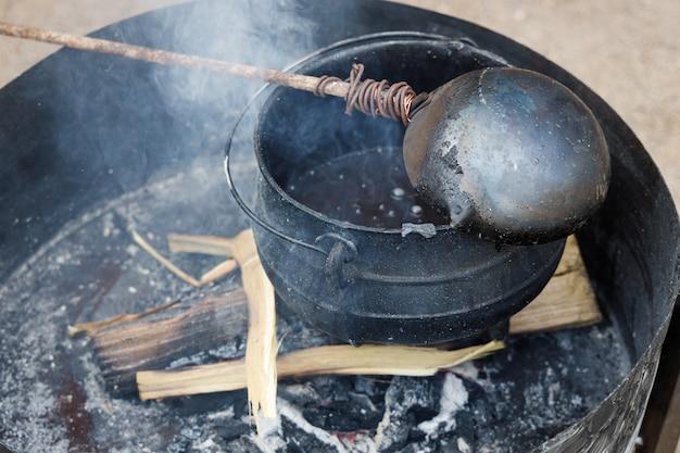 Pentola nera in cui viene sciolta la cera per produrre candele