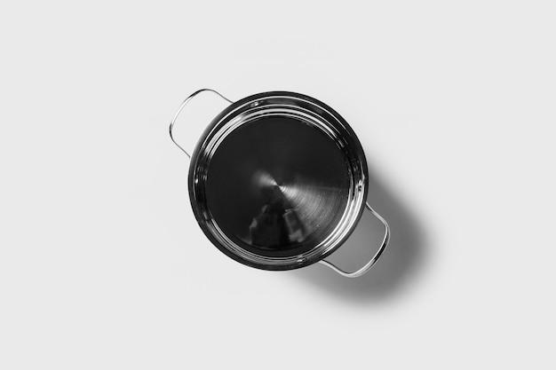 Pentola vuota di metallo senza coperchio su uno spazio luminoso isolato. vista dall'alto, piatto