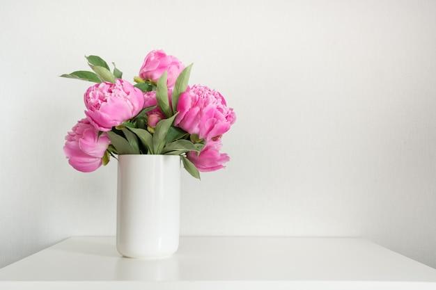 Peonia rosa in vaso su bianco. copia spazio per il testo. festa della mamma.