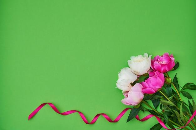 Peonie bianche e rosa decorate con nastro rosa su sfondo verde. sfondo vacanza, copyspace, vista dall'alto