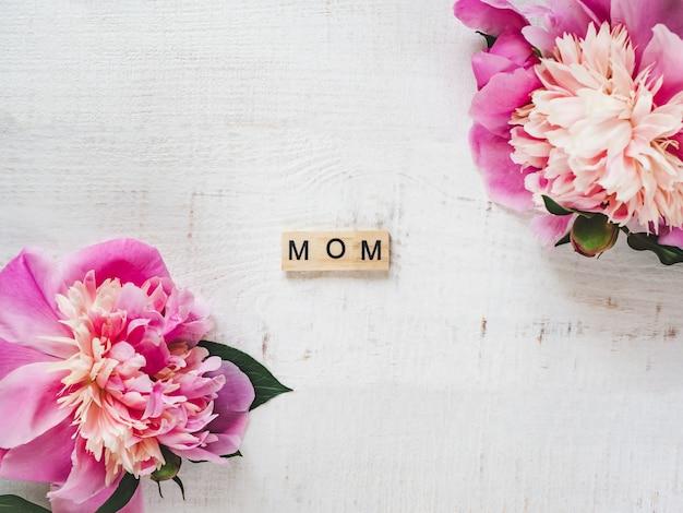 Peonie colorate e parola mamma su uno sfondo bianco