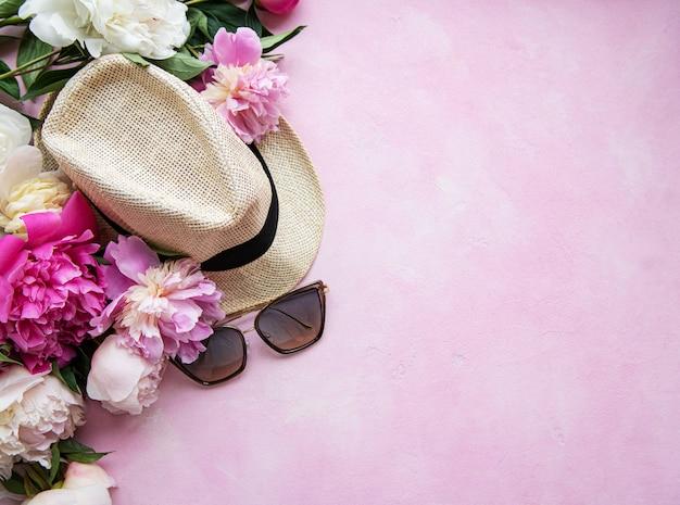 Peonie rosa e cappello su uno sfondo di cemento rosa