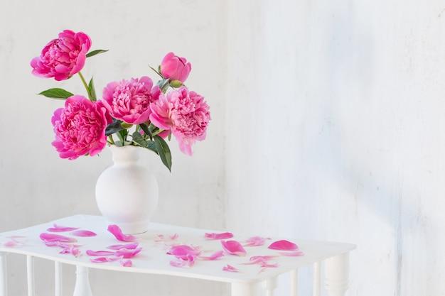 Peonie rosa in vaso su legno bianco vintage