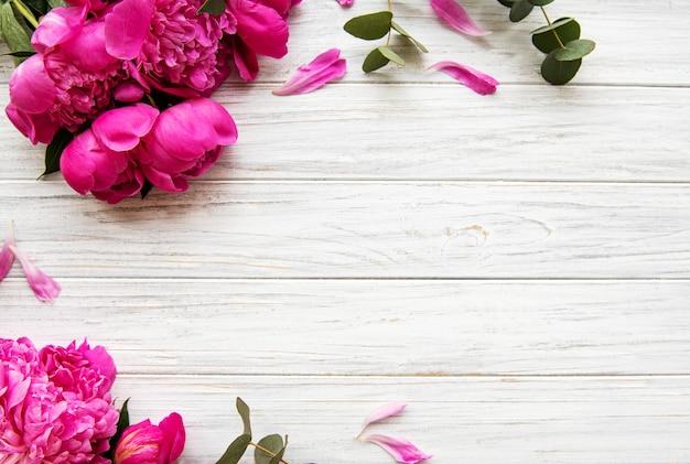 Peonie rosa su tavola di legno
