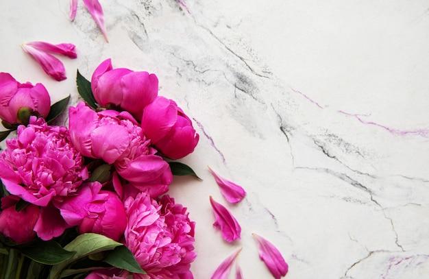 Peonie rosa su uno sfondo di marmo