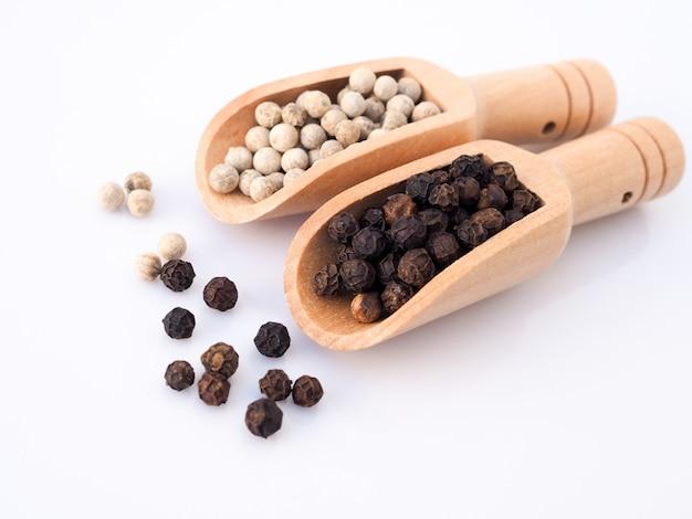 Pepe bianco e pepe nero in cucchiaio di legno isolato su superficie bianca.
