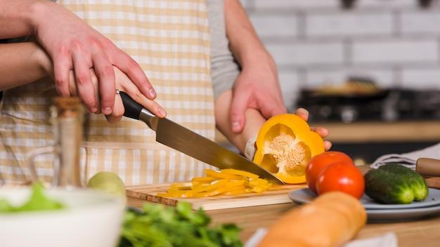Pepe di taglio delle coppie in cucina insieme