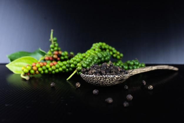 Pepe e pepe nero freschi in cucchiaio di legno su fondo nero.