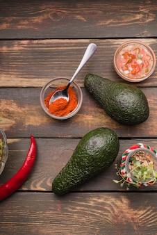 Pepe e salsa in ciotole tra avocado e peperoncino