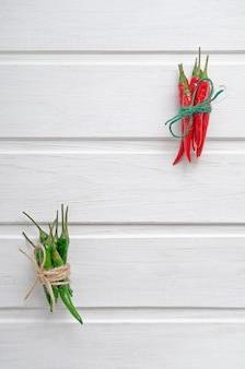 Peperoncini caldi rossi e verdi multicolori legati con un flagello su un fondo o su una tavola di legno bianco con il posto per testo.