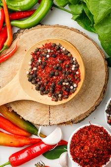 Peperoncini con aglio, i granelli di pepe, il pepe di cayenna, la pianta e il bordo di legno su bianco