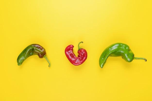 Peperoncini rossi brutti alla moda su giallo, stile naturale minimale, pop art, cibo creativo