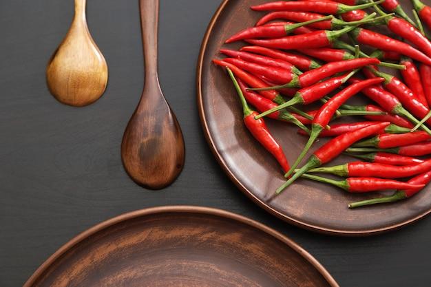 Peperoncini rossi caldi nel piatto marrone delle terraglie