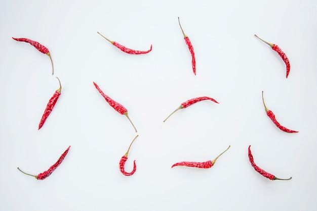 Peperoncini rossi disposti su sfondo bianco