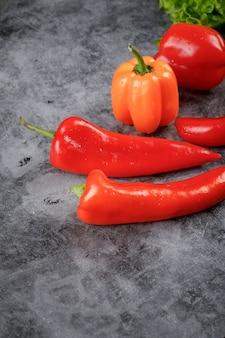 Peperoncini rossi e peperoni dolci sul tavolo di pietra.