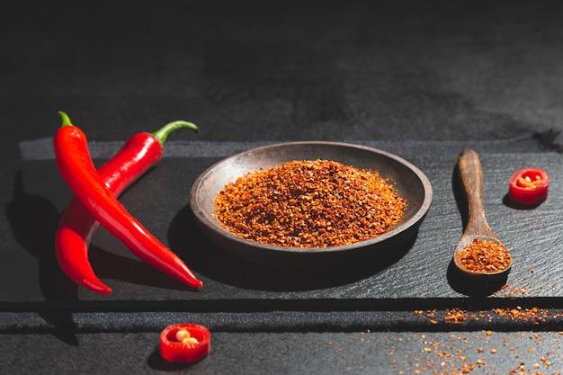 Peperoncini rossi e polvere di peperoncini rossi rossi sul piatto e sul cucchiaio di legno